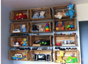 nichos de caixas de feira presos a parede para guardar brinquedos em quarto infantil
